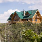 Exterior photo of handcrafted log home with green metal roof, steep pitched gables and small doghouse dormers on either side of main roof line.