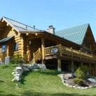 Exterior of handcrafted Cedar log home with covered porch and log railings.