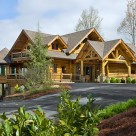 Exterior photo of luxury log home with multiple roof lines octagonal sunroom and beautiful portico.