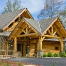 Log portico with log trusses and kneebraces set on square stone piers in paved driveway.