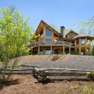 Exterior photo of luxury log home with large glass bay front, octagonal sunroom and walkout lower level.