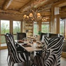 Zebra stipe chairs at dining room table in handcrafted log home with french doors showing view of southern forest.