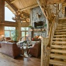 Great room of luxury log home with curved log staircase, massive stone fireplace and massive bay windows surounded by large log columns.