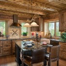 Custom kitchen cabinetry in handcrafted log home kitchen with exposed log ceiling beams and copper vent hood over range.