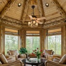 Close up photo inside log octagonal sunroom with ceiling fan over coffe table and log rafters with t&g pine for ceiling.