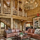 Handcrafted log home great room with massive antler chandelier, leather sofa's and log posts at loft edge supporint log roof beams.