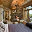 Master bedroom in custom log home with stone fireplace in corner and glass wall with view into sourthen USA forest.