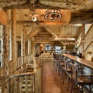 Open loft in luxury log home with long bar and barstools and log posts supporting log beams in ceiling.