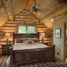 Loft bedroom with king bed backed up to full log gable with exposed log purlins above.