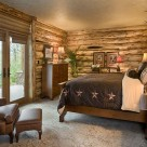Basement bedroom with log siding interior, king size bed and french doors leading to patio outside.