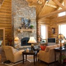 Large stone fireplace with log mantle in great room of handcrafted log home.