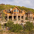 Exterior view of luxurious Steamboat Springs Colorado log home with massive stone pillars supporting full width deck and turrets on each side of home.