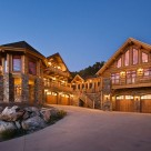 Stunning twilight photo of luxury log home and log guesthouse set above 5 car stone garage. Octagon sunroom set on stone pillars to side of driveway.