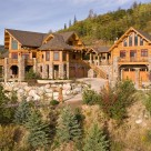 Exterior photo of luxury log home and guesthouse attached by breezway in mountain setting.
