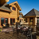 Patio chairs on deck of handcrafted log home with red framed windows and doors and log framed octagon sunroom.