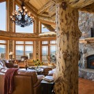 Luxury log home greatroom with stone fireplace with log mantle, massive log post and beam framing large windows with spectacular mountoin views.