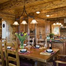 Heavy wood dining table and chairs with chandelier above and luxury log home kitchen in background with exposed logs and pine board ceiling.