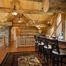 Fancy bar with barstools in open loft of log home with massive logs, pine ceiling over exposed log beams, hardwood floors with area rug.