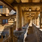 Beautiful log breezway with massive stone walls supporing large log columns, header logs and roof logs with log home in background.