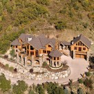 Aerial view of luxury log home with log guesthouse attached by breezway on mountainside in Steamboat Springs Colorado.