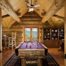 Custom made pool table in loft of handcrafted log home viewed through open glass doors with full log gable and exposed roof beams.