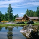 Exterior of custom log home with prow front viewed from across pond