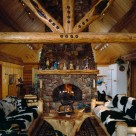 Interior great room in custom log home with log truss and stone fireplace.