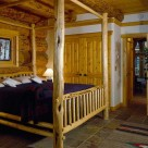 King size log bed set in master bedroom with slate floors of handcrafted log home built with massive logs.