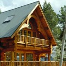 Close up exterior photo of log home balcony framed in timber hammerbeam truss and log rails with french doors in gable behind.