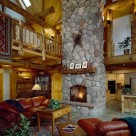 Great room with soaring cathedral ceilings with red leather sofa and log endtables set on area rug in front of massive stone fireplace with antique snowshoes hung above log mantle.