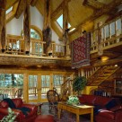 Custom log home greatroom with cathedral ceilings supported by character log posts and log purlins. Open loft above with log railings and archtop window in gable. View to Colorado forest through frenchdoors at end wall of log home with log staircase to loft on right.
