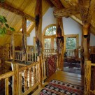 Open loft in custom log home, character logs support log purlins and log railings trim loft edge. White wall in gable with french doors leads to balcony