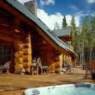 Exterior close up photo of handcrafted log home built with massive logs. Jacuzzi tub set into deck with log rails,