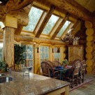 Dining room in luxury log home with slate floors set under log archway with massive logs and glass walls framed in log posts.