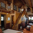 Interior of rustic log cabin with stairs to loft and Navaho rugs on log railings