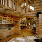 Interior of handcrafted log home with custom cabinets and view through log archway to stone fireplace in greatroom with transom windows.