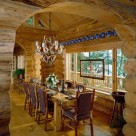 Massive log slab dining table with rustic log chairs and antler chandelier set in handcrafted log home dining room viewed through log archway