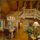 Interior of handcrafted log home with massive log plank dining table, antler chandelier, log stairs to open loft with log railings and cathedral ceilings supported by log posts and purlins.