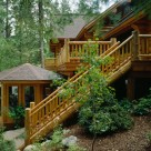 Exterior log staircase with log railings decending from deck of handcrafted log home to gazebo spa on Swan Lake MT.