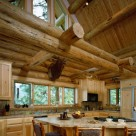 Custom log home kitchen with custom cabinets, tile counters, breakfast bar with log barstools. Exposed log beams above with glass in gable and elk head mount on wall.