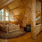 Log bed set on oval area rug in open loft of custom log home with log post and beam ceiling and white gable with trapezoid windows.