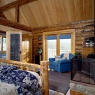 Master bedroom in Colrado log home with wood stove near a log bed and views through french doors.