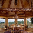 Beautiful octagonal dining room in handcrafted log home with round dining table and antler chandelier above. Exposed log beams with pine boards above for ceiling.