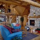 Log home greatroom with stone fireplace, wood floors and blue sofa on throw rug.