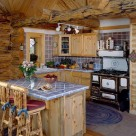 Log home kitchen with antique cook stove, blue tile counters and breakfast bar with log barstools.