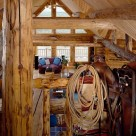 View from loft in custom log home with saddle and lariat on log rail in foreground and great room below.