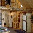 Interior of log home with spiral staicase leading to open loft beside antique looking refrigerator.
