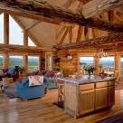 Interior of handcrafted log home with bay dining room and glass wall in great room with wood floors and exposed log ceiling beams