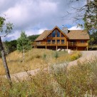 Exterior of handcrafted log home with bay dining room and glass wall in greatroom