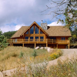 Exterior of log home with bay dining room and glass wall in great room